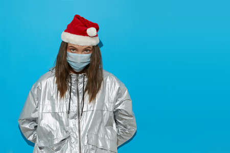 Serious female wearing Santa hat and protective mask standing on blue background in studio and looking at camera