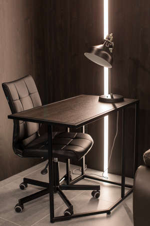 Comfortable chair placed near desk with lamp in corner of illuminated modern workplace