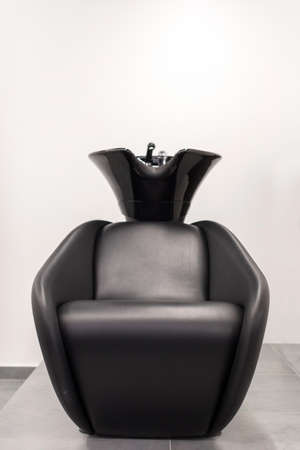 Comfortable black armchair with sink for hair washing located inside modern hairdressing salon Stockfoto