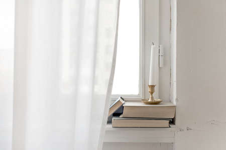 Golden candlestick with candle placed on pile of books on windowsill in room