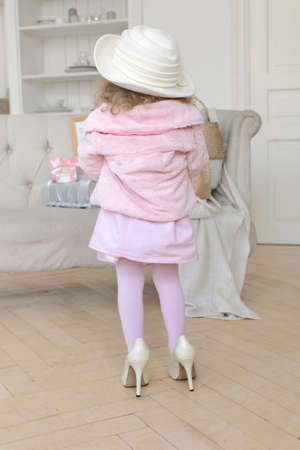 Back view of unrecognizable little girl in pink clothes and high heeled shoes standing in bright room at home and pretending being adult woman Stockfoto