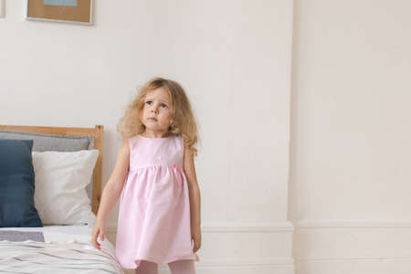 Tender little girl in pink dress standing in cozy bedroom and looking away