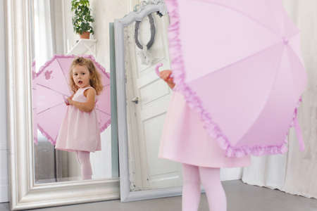 Adorable little child in pink dress and with umbrella looking in mirror while standing in cozy room
