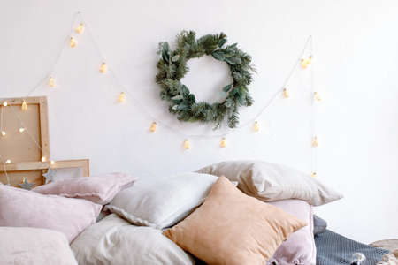 Cozy bed with pile of cushions in bedroom decorated with Christmas garland and wreath