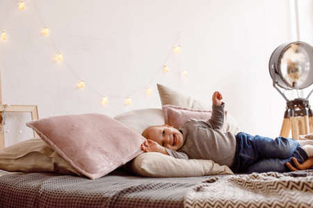 Laughing little child lying on cozy bed and having fun while looking away and enjoying weekend