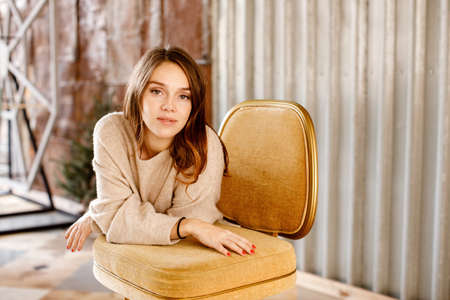 Charming female wearing cozy sweater leaning on chair and looking at camera while standing in contemporary room