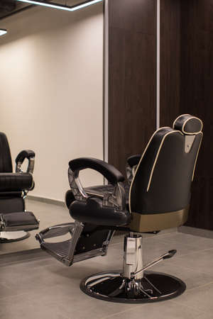 Comfortable chair placed near clean mirror inside modern hairdressing salon with stylish interior Stockfoto