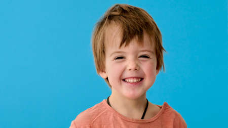 Adorable little boy with blond hair in orange t-shirt smiles posing for camera on bright turquoise background close view