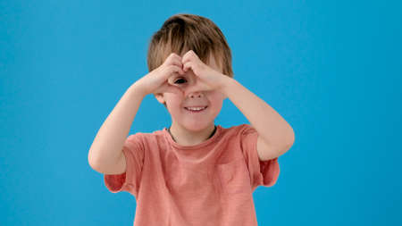 Cute little kid in orange t-shirt makes heart shape with fingers posing for camera on bright turquoise background close view Stockfoto