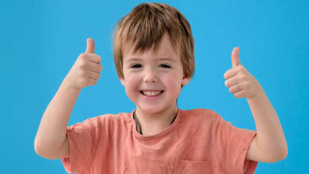 Funny little boy in orange t-shirt smiles and shows thumbs-up posing for camera on bright turquoise background close view