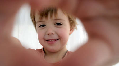 Playful little kid in orange t-shirt makes heart shape with fingers as frame on camera lens against white curtain in room closeup Stockfoto