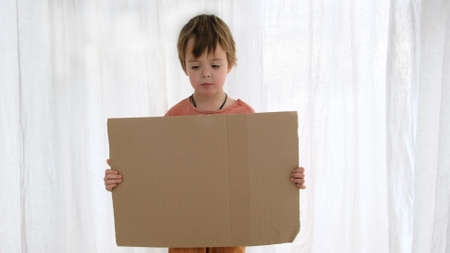 Upset little boy in orange holds large cardboard sheet with space for template standing near white curtain in light room