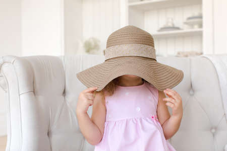 Playful little child sitting on sofa and covering face with adult sunhat while having fun