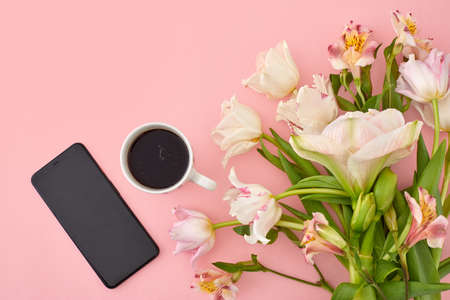 White cup of coffee with tulip and smartphone on pink background copy space