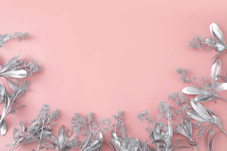From above of silver flowers in shape of frame arranged on pink background in studio