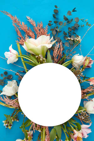 From above of bouquet of various plants and flowers arranged on vivid blue background with white blank circle in studio