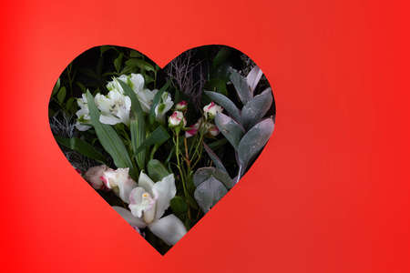 Hole in red paper in shape of heart through with flowers and leaves are visible. Happy valentines day concept