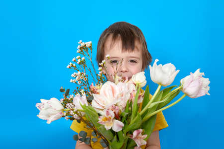 Cute boy smiling with a bouquet of tulip flowers as a gift on a blue background in studio