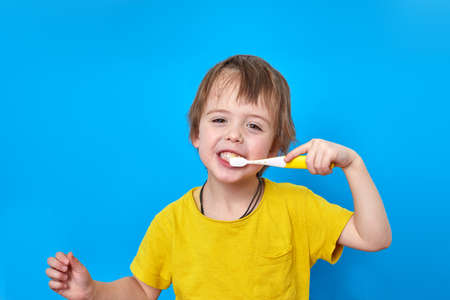 Smiling handsome little boy is brushing his teeth with brush on blue background Stockfoto - 161830776