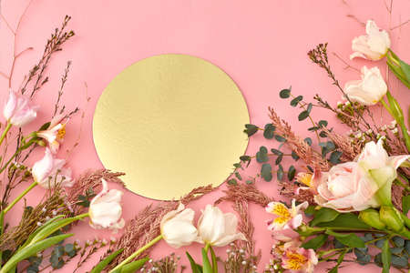 High angle of assorted blooming flowers and plants arranged on pink background with golden shiny round paper Stockfoto