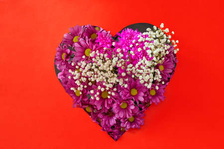 Top view of bright blooming pink flowers with gypsophila in heart shaped gift box for festive event