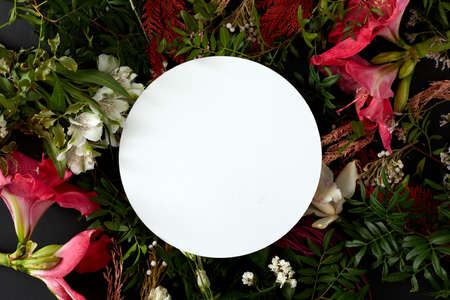 Top view composition with various fresh blooming flowers with green foliage arranged around blank white round plate