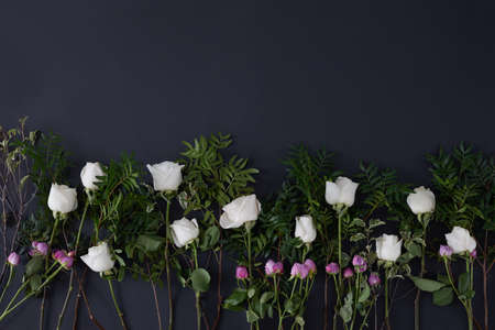Top view of many white and pink roses with green leaves placed on black background
