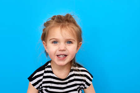 Close-up studio shot of a lovely little girl in t-shirt posing against a blue background. Looks at the camera and smiles