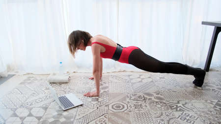 Wide shot of obese smiling woman doing push-ups at home on exercise mat. Side view portrait of plus-size Caucasian sportswoman training at home using online tutoring. Weight loss and sport concept.