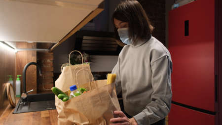 Young short haired housewife puts large paper bags with products on countertop in protective mask in kitchen at home