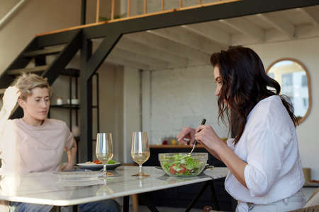 Side view of young female serving salad from bowl while having romantic dinner with girlfriend at home