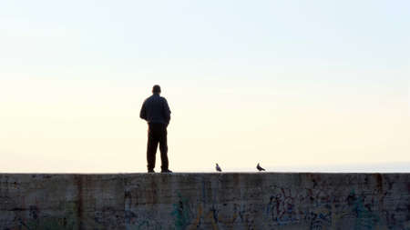 Dark silhouettes of man and pigeons standing on large stone pier and looking at sunset from sea beach in tranquil evening