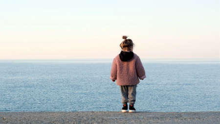 Cute little girl in fluffy pink jacket with black hood looks at tranquil water standing on sea beach back view