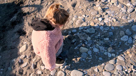 Blonde little girl with pigtail in fluffy pink jacket plays with sand and stones on sea beach at autumn sunset close upper view Stockfoto