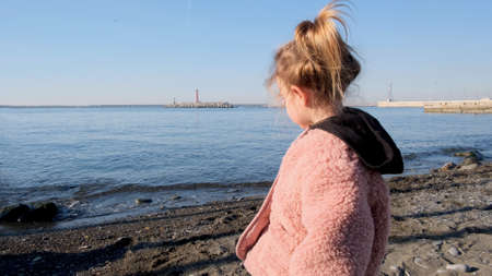 Cute little girl in fluffy pink jacket with black hood looks at tranquil water standing on sea beach at autumn sunset closeup