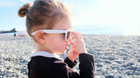 Funny blonde little girl in black blouse plays with stylish sunglasses spending time on sea pebble beach back light Stockfoto