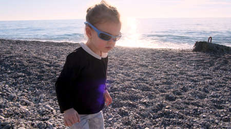 Funny blonde little girl in black blouse plays with stylish sunglasses spending time on sea pebble beach at sunset back light