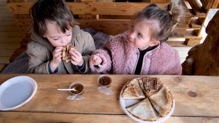 Adorable little boy and girl eat delicious fresh crepes with fruit jam sitting at rustic wooden table in comfortable cafe Stockfoto