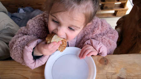 Adorable little girl eat delicious fresh crepes sitting at rustic wooden table in comfortable cafe