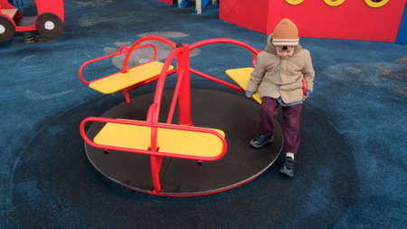 Adorable toddler boy in warm hat and jacket rides on small merry-go-round on contemporary playground in apartment building yard