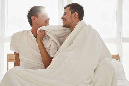 Happy young men wrapping in warm blanket and smileing at each other while resting on comfortable bed in morning in cozy bedroom