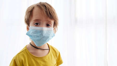 Young boy in mask white background looking at camera . Masked face boy protect health . Portrait little child in medical masks. Cute kid in quarantine epidemic Stockfoto