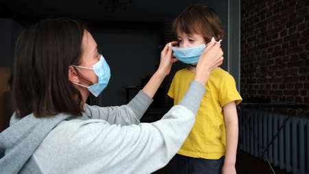 Mother with protective mask hugs son at home outbreak quarantine. Mother putting protective face mask on her child pandemic . Side view of adult woman putting on medical mask on little boy Stockfoto