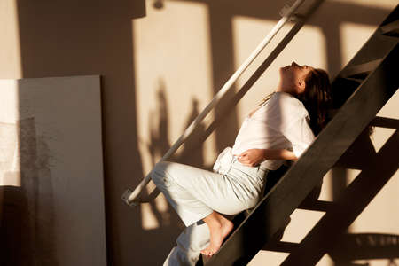 Side view of sensual young female with dark hair in casual clothes leaning on stairs with closed eyes during rest in art studio Stockfoto
