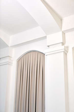 From below of house interior details with white walls and columns and beige curtains