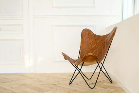 Interior of room with comfortable leather chair on parquet floor and white walls