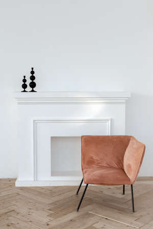 Interior of simple room with white wall over parquet floor and soft creative armchair
