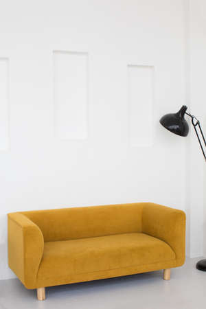 Comfortable yellow couch and floor lamp placed in living room with white walls in minimal style Stockfoto