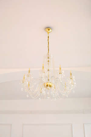 From below of classic elegant golden chandelier with crystal pendants hanging on white ceiling in light room
