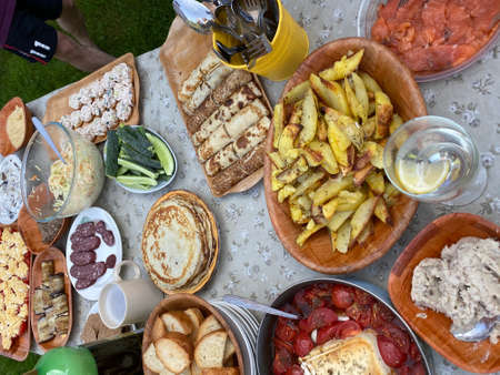 From above of various types of homemade snacks and dishes served on rustic table during outdoor summer party